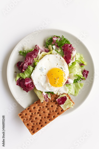 Sticker Healthy breakfast on plate consisting of fried egg, red and green lettuce and crispy bread