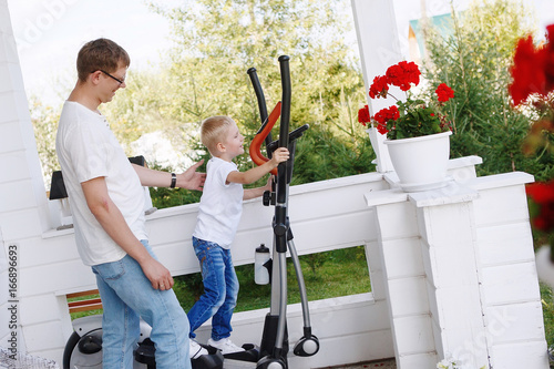 Little boy on a treadmill with his father on the veranda of his house