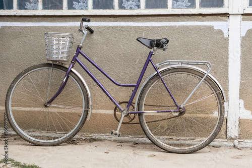 Poster Fiets Bicycle with a basket in the courtyard of a rural house
