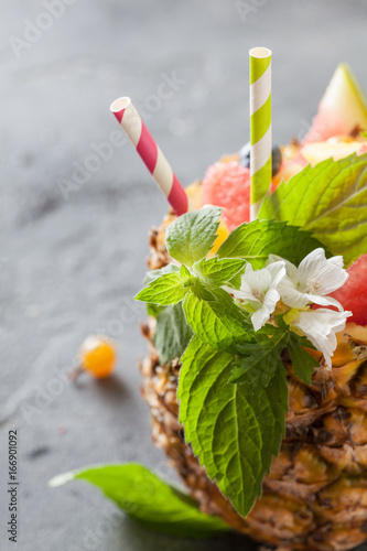 Exotic fruit salad served in half pineapple on dark background