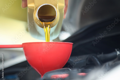 fototapeta na ścianę Motor oil pouring, Pouring oil lubricant motor car from bottle