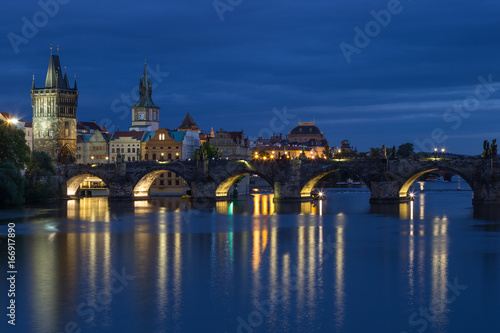 Lit Charles Bridge (Karluv most) and old buildings at the Old Town and their reflections on the Vltava River in Prague, Czech Republic, at dusk.