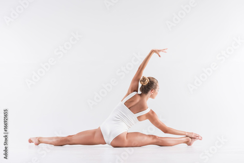 Youthful sport lady performing stretching workout Poster