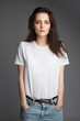 attractive female model front view in blank white t-shirt and jeans isolated on gray background