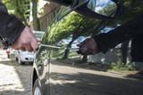Eine Mann zerkratzt den Lack an einem Fahrzeug mit einem Schraubendreher - 166921828