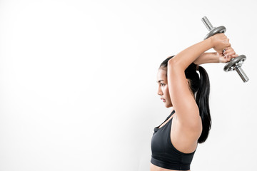 sporty girl lifting dumbbells  on white background. © pigprox