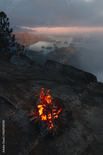 Man sitting on the edge with campfire above bay with islands and forests in cloudy weather from top view in the evening