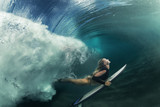 A blonde surfer girl underwater doing duck dive holding surfing board left behind air bubbles in blue water background under big ocean wave