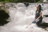 Beautiful young traveling woman enjoy the waterfall.vintage tone hipster style and soft focus.