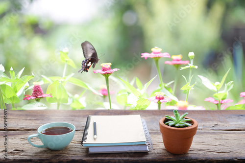 Red tea and plant with notebook and butterfly with pink flower