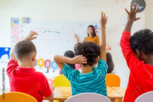 Fototapeta Preschool kid raise arm up to answer teacher question on whiteboard in classroom,Kindergarten education concept