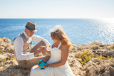Bride puts on the ring on the groom's finger. Wedding couple on the beach