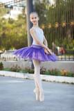 Young beautiful ballerina dancing outdoors in a park. Full length portrait beautiful caucasian girl. - 166953038