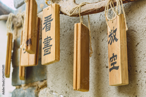 close-up of bamboo wishes hanging on wood against wall in temple.