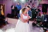 Newly married couple dancing on their wedding party with heavy smoke and multicolored lights on the background. - 166968814