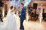 Newly married couple dancing on their wedding party with heavy smoke, multicolored lights and fireworks on the background. - 166969205