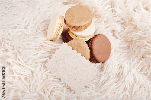 Foto op Canvas Macarons Macarons with paper blank copy space. Macarons of coffee color on a soft background, with a blank for a design.