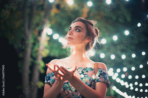 Poster Beautiful young woman smiling and talking garlands of lights at city