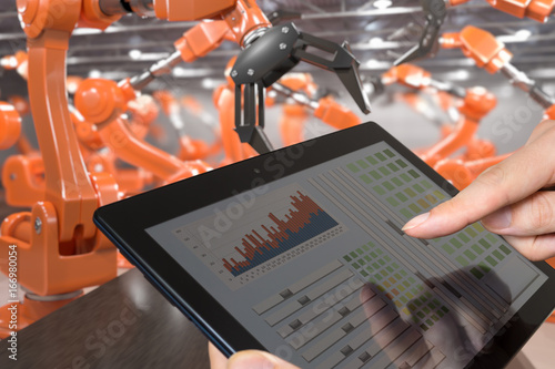 Man is controlling robotic arms with tablet. Automation and Industry 4.0 concept.