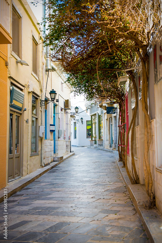 Narrow stone street with trees on the walls leading to center of Syros island, Cyclades , Greece