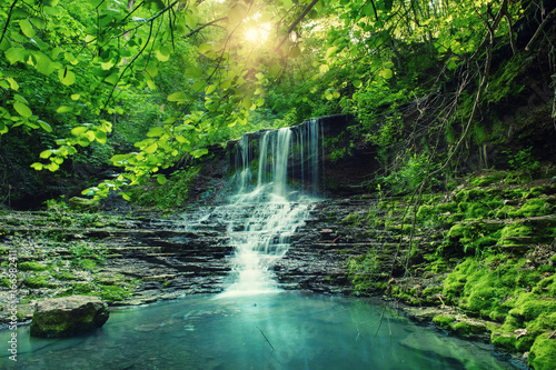 Beautiful mountain rainforest waterfall with fast flowing water and rocks, long exposure. Natural seasonal travel outdoor background with sun shihing - 166982411