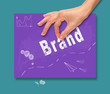 A hand picking up a Brand concept on a colorful drawing board.