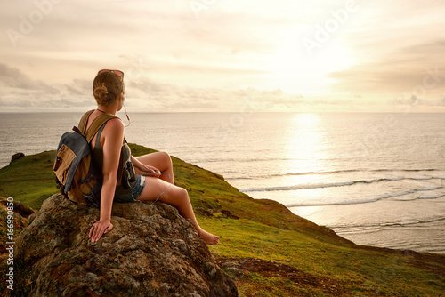 Hiker with backpack enjoying sunset listening to music on peak of mountain.