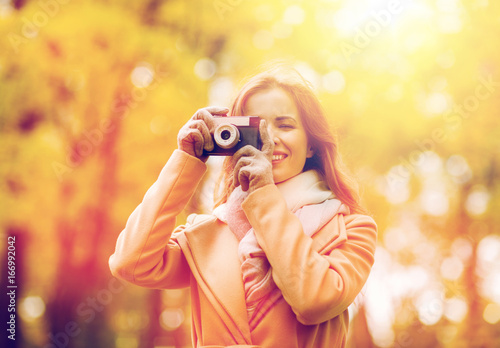 woman photographing with camera in autumn park