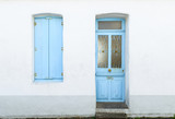 White house facade with pastel blue blinds and door in Noirmoutier island, France