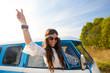 Quadro happy hippie woman showing peace in minivan car