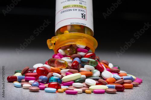A prescription pill bottle spilling out an assortment of pills