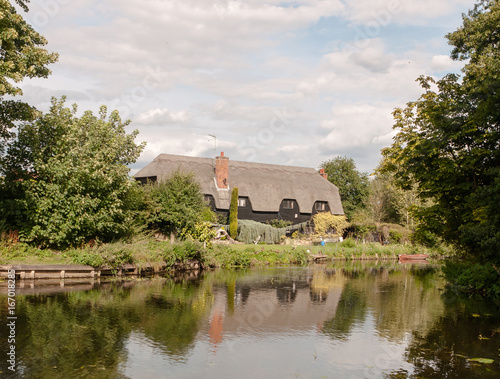 old english historic cottage seen over a lake with reflections Poster
