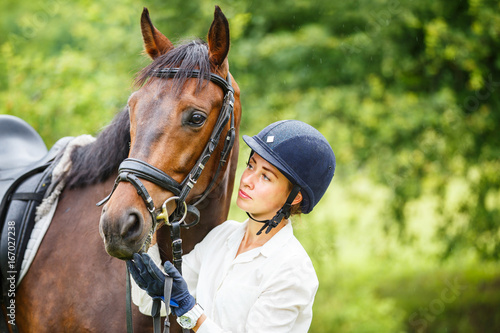 Young smiling rider woman in helmet holding bay horse by bridle Poster