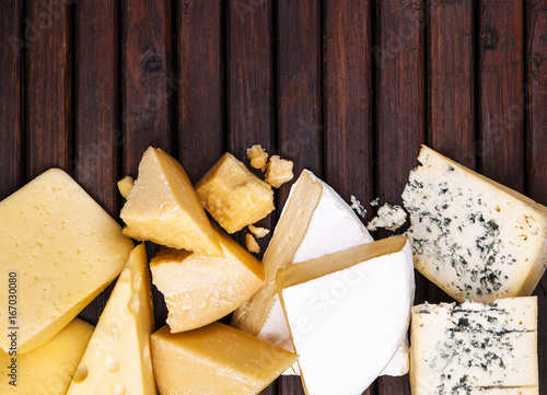 Various types of cheese on rustic wooden table, top view Poster