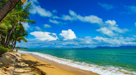 Sunny day with blue cloudy sky at tropical Maenam beach, Koh Samui, Thailand. Young couple is resting on the beach