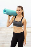 Sport as style of life. Attractive young woman in sports clothing keeping yoga mat and smiling while standing on seaside wooden pier.