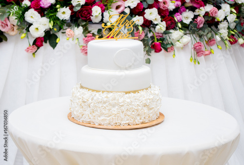Beautiful white wedding cake at wedding reception