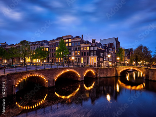 Poster Amterdam canal, bridge and medieval houses in the evening
