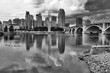 Cloudy morning in Minneapolis. Minneapolis downtown skyline and Third Avenue Bridge above Mississippi river in black and white. Midwest USA, Minnesota state.