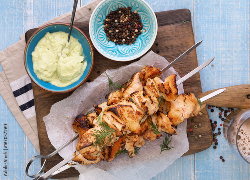 Barbecued chicken breast skewers with avocado sauce on wooden background - 167057260