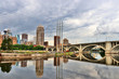 Cloudy morning in Minneapolis. Minneapolis downtown skyline and Third Avenue Bridge above Saint Anthony Falls, Mississippi river. Midwest USA, Minnesota state.
