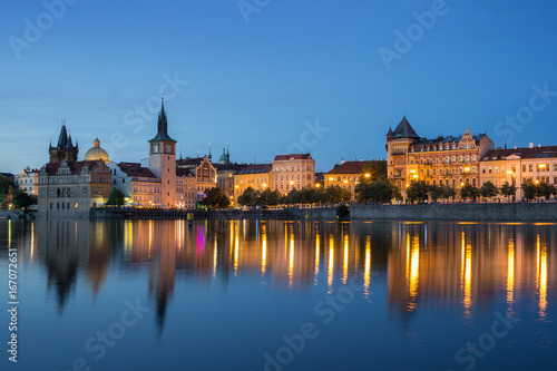Lit old buildings at the Old Town and their reflections on the Vltava River in Prague, Czech Republic, at dusk.