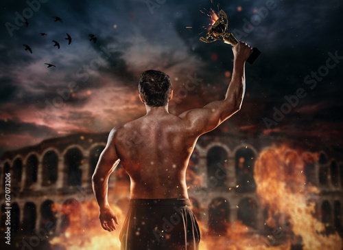 Zobacz obraz Back view of muscular man holding burning trophy cup, antique colosseum on background.