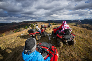 Group of people riding a off-road vehicles on a mountain road under beautiful sky with clouds in autumn day