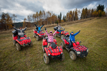 Young people in winter clothes with raised hands up on red atv off-road vehicles on a countryside trail in nature under the sky with clouds. Top view
