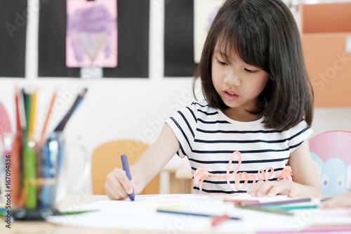 Fototapeta Girl drawing color pencils in kindergarten classroom, preschool and kid education concept