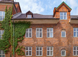 Part of a beautiful house in the city of Copenhagen. Brick building wall with windows is entwined with ivy