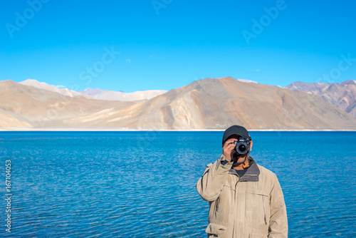 Tourist man in brown coat taking photography with camera at Beautiful Pangong la Poster