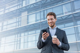Businessman holding mobile cell phone using app texting sms message wearing suit. Young urban professional man using smartphone at office building.