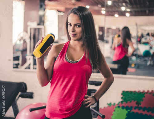 Poster Attractive young brunette posing at the gym, holding water bottle